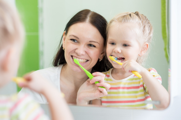 Mother And Child Daughter Brushing Teeth Together